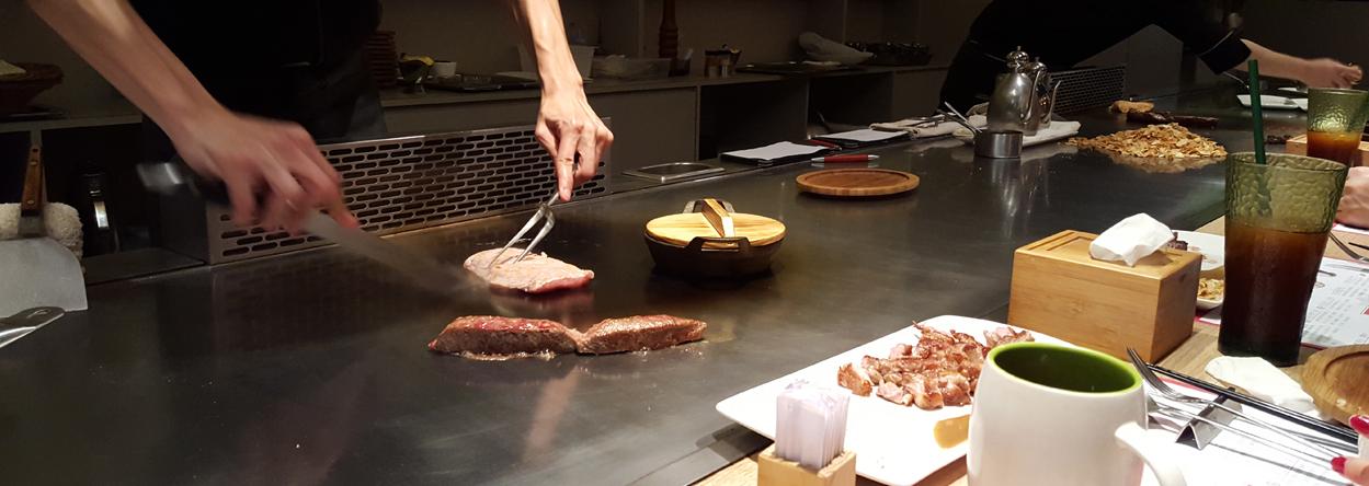 Koch bei der Zubereitung eines Teppanyaki Gerichtes